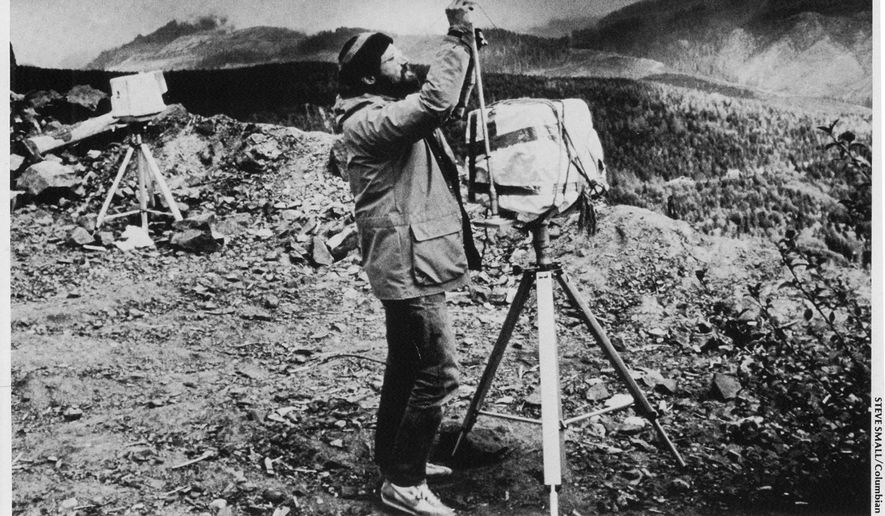 In a 1980 photo, photojournalist Reid Blackburn adjusts one of two remote-controlled cameras on Mount St. Helens. Blackburn, one of 57 people to die in the eruption, was loaned from the Columbian newspaper to National Geographic to operate a pair of remote-controlled cameras. One was with the 27-year-old photographer at the camp dubbed Coldwater I, about 8 miles northwest of the volcano. (Steve Small/The Columbian via AP)