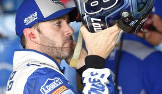 Jimmie Johnson puts his helmet on to re-enter his car during final practice for the NASCAR Sprint Cup series auto race, Saturday, May 14, 2016, at Dover International Speedway in Dover, Del. (AP Photo/Nick Wass)