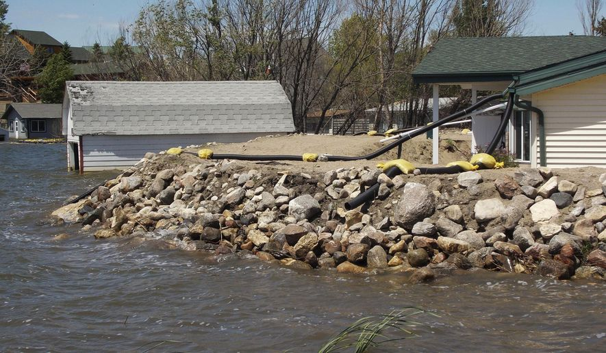 FILE - In this June 9, 2014 file photo, waves pound against a rock-covered dike built around a home on the southern shore of Rice Lake, a rural lake near Minot, N.D. Property owners around the lake are getting a reprieve from flooding this spring, and efforts to battle the chronic problem are in good financial shape. Rice Lake rose for five straight years, causing more than $3 million in losses. This spring, its level is up less than half a foot. (Kim Fundingsland/The Daily News via AP, File) MANDATORY CREDIT