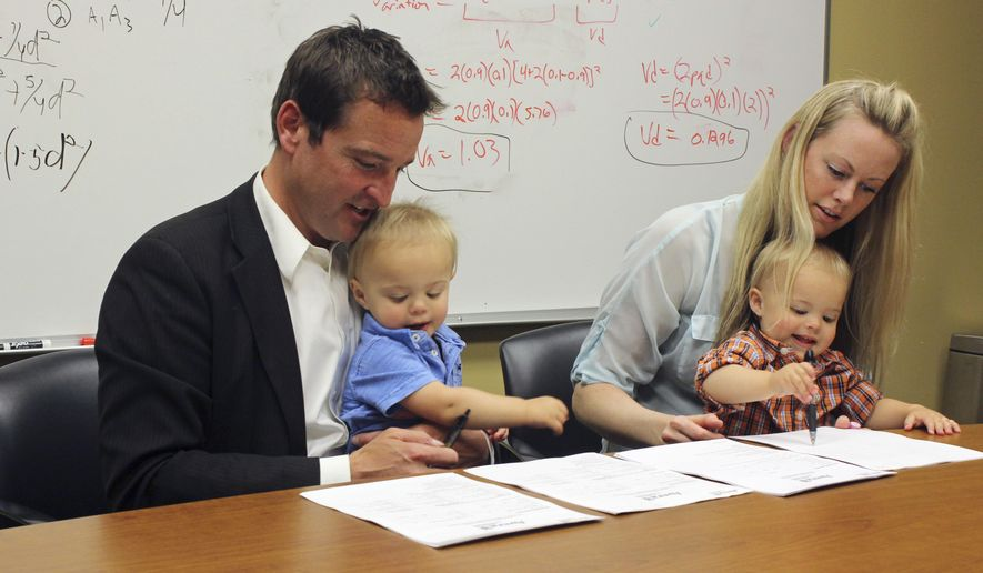 Craig McCarthy and Rebecca Amble read over consent forms to allow their 16-month-old identical twins, Kamper, left, and Sayers to be part of the Avera Twin Register on Wednesday, May 18, 2016, in Sioux Falls, S.D. Sioux Falls-based Avera Health on Wednesday launched the register hoping twins who live in the Midwest will contribute DNA to the project aimed at gaining insights into traits and diseases specific to the region. (AP Photo/Regina Garcia Cano)