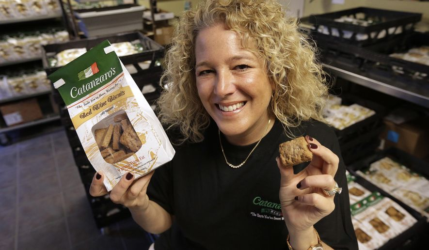 In this Tuesday, May 17, 2016 photo Kristen Catanzaro, of North Providence, R.I., displays wine biscuits in the packing room of her baking facility, in Pawtucket, R.I. The Rhode Island Senate is scheduled to vote Wednesday, May 18 on a bill that would allow bakers to get a special license to bypass existing wholesale alcohol restrictions to purchase up to 2,000 gallons of wine a year if it's used to make the traditional cookies. (AP Photo/Steven Senne)