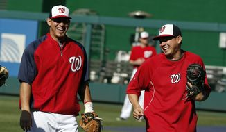 Washington Nationals catchers Wilson Ramos and Jose Lobaton run off the field before a baseball game against the Los Angeles Dodgers at Nationals Park, Tuesday, May 6, 2014, in Washington. (AP Photo/Alex Brandon)