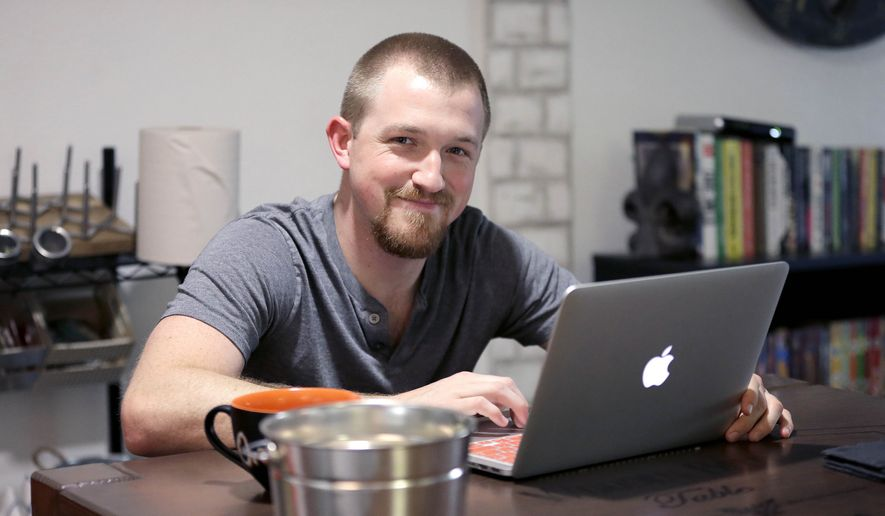 In this Wednesday, May 18, 2016, photo, Mitchell Timme works from his laptop computer at his home in Phoenix. Two-thirds of Americans would have difficulty coming up with the money to cover a $1,000 emergency, according to an exclusive poll conducted by The Associated Press-NORC Center for Public Affairs Research. Timme said that his wages have remained basically flat for the last few years while his cost of living has increased. (AP Photo/Matt York)