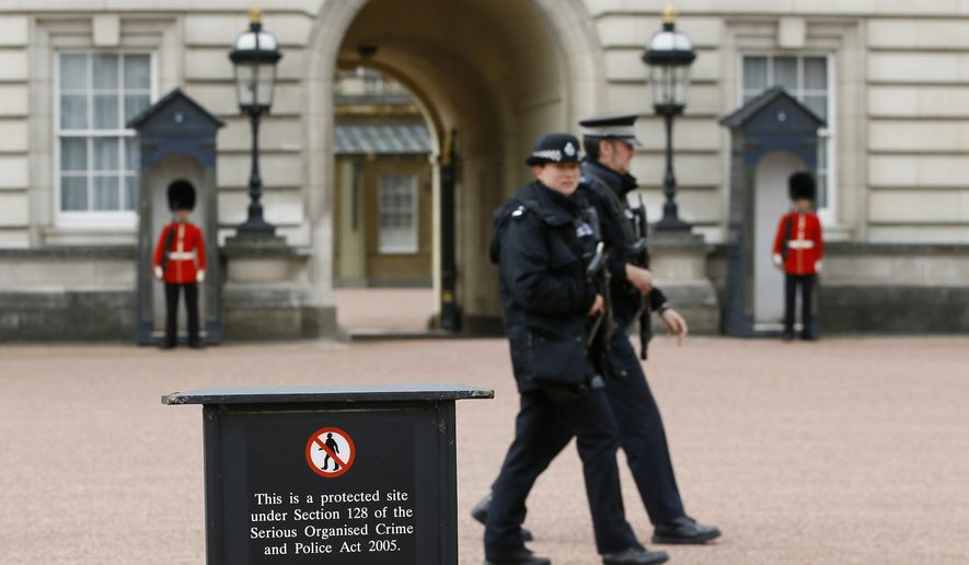 Armed police officers patrol in the grounds of Buckingham Palace in London, Thursday, May 19, 2016. British police say they have arrested a man who scaled a wall and got into the grounds of Buckingham Palace. The Metropolitan Police force says a 41-year-old man was detained in the palace grounds Wednesday evening on suspicion of trespassing on a protected site. (AP Photo/Kirsty Wigglesworth) ** FILE **