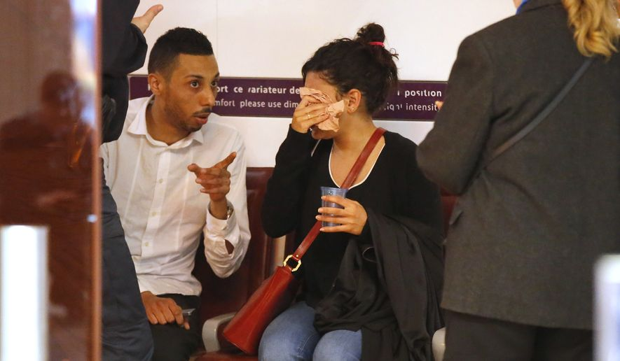 A relative of the victims of the EgyptAir Flight 804 wipes her tears as she is comforted by unidentified people at Charles de Gaulle Airport outside of Paris, Thursday, May 19, 2016. Egyptian aviation officials say an EgyptAir flight from Paris to Cairo with 66 passengers and crew on board has crashed. (AP Photo/Michel Euler)