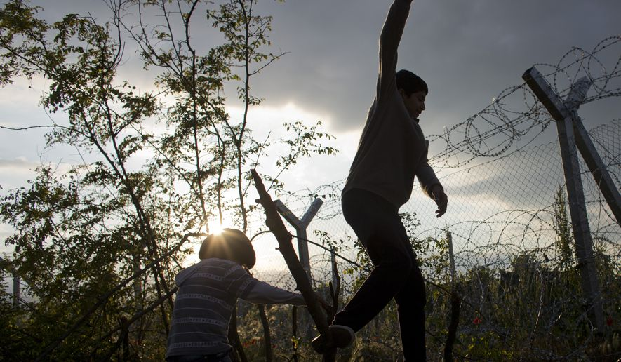 Amir (right) and Mohammed, refugees from Syria, play in front of a barbed-wire fence on the Macedonian border, in Idomeni, Greece, on May 19, 2016. Thousands of stranded refugees and migrants have camped in Idomeni for months after the border was closed. (Associated Press) **FILE**