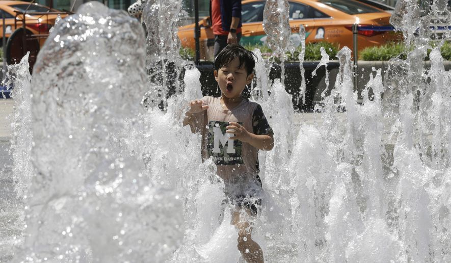 A boy plays in a fountain to beat the summer heat in Seoul, South Korea, Thursday, May 19, 2016. A heat wave warning was issued in Seoul as temperatures soared above 32 degrees Celsius (90 degrees Fahrenheit). (AP Photo/Ahn Young-joon)