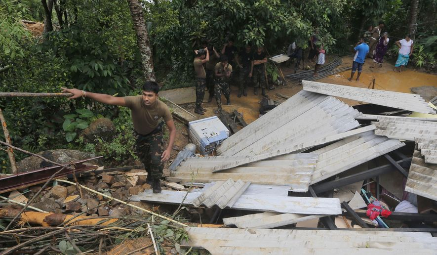 A Sri Lankan army soldier walks on the debris of a house during a search operation in Elangapitiya village in Aranayaka, some 72 kilometers (45 miles) north of Colombo, Sri Lanka, Thursday, May 19, 2016. Heavy rains Thursday continued to pound the central Sri Lankan region where at least three villages have already been swallowed by mountains of mud, forcing army soldiers and police to suspend rescue work. (AP Photo/Eranga Jayawardena)