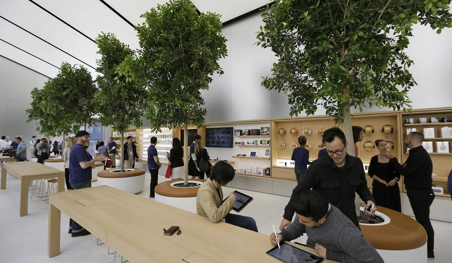 """People try products in the """"Genius Grove"""" during a preview of the new Apple Union Square store, Thursday, May 19, 2016, in San Francisco. Apple is getting ready to unveil a stylish new product that's not for sale, a new look for its stores. The iPhone maker is overhauling its nearly 480 stores worldwide, starting with its new location in San Francisco. (AP Photo/Eric Risberg)"""