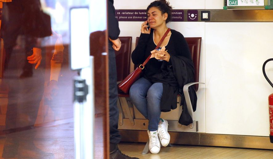 A relative of the victims of the EgyptAir flight 804 that crashed, reacts as she makes a phone call at Charles de Gaulle Airport outside of Paris, Thursday, May 19, 2016. Egyptian aviation officials say an EgyptAir flight from Paris to Cairo with 66 passengers and crew on board has crashed. (AP Photo/Michel Euler)
