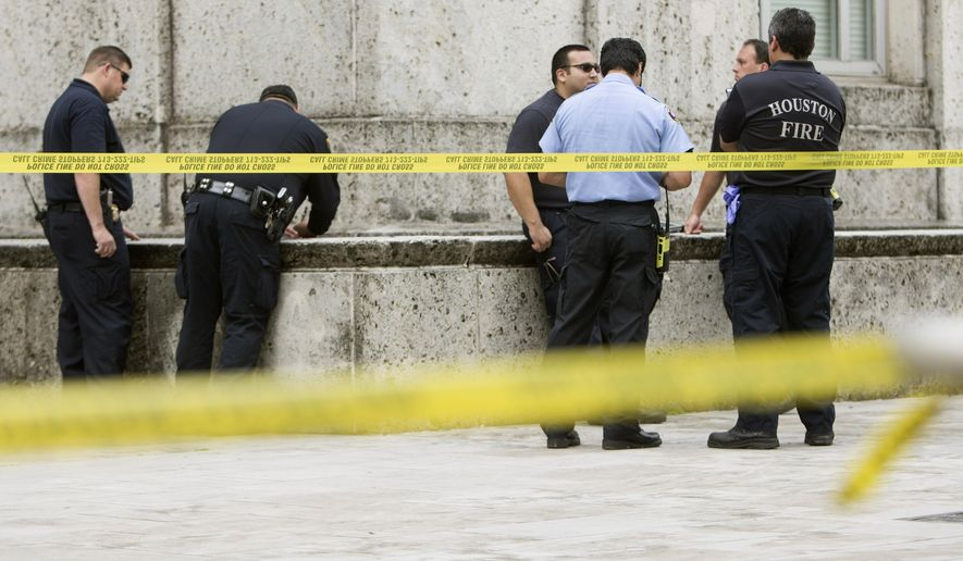 Police investigate the scene outside City Hall where a man died after falling off a ledge Wednesday, May 18, 2016, in Houston. ( Brett Coomer/Houston Chronicle via AP) MANDATORY CREDIT