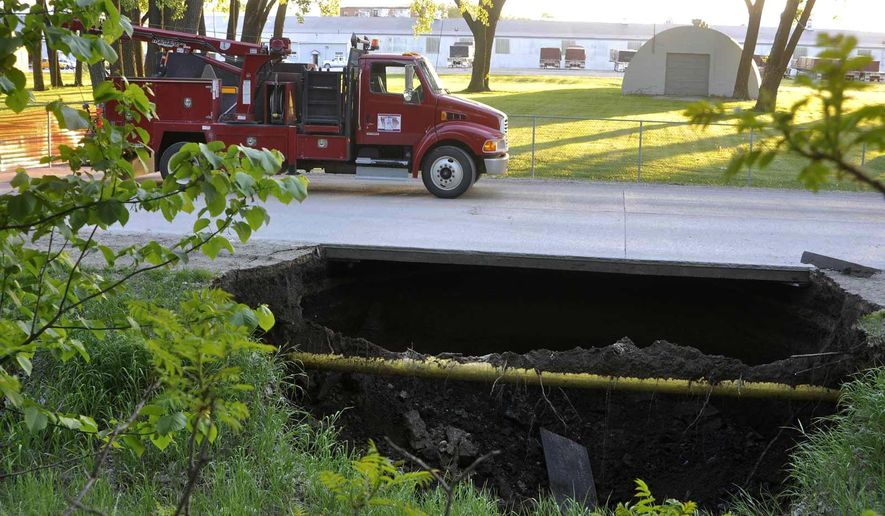 In this Wednesday, May 18, 2016 photo, a sinkhole forces the closure of a street in Fort Dodge, Iowa. (Chad Thompson /The Messenger via AP) MANDATORY CREDIT
