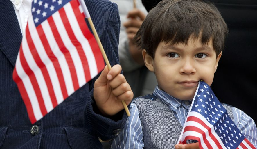Iker Velasquez, 4, who came from Honduras with his parents, holds a U.S. glad as he listens while Rep. Luis Gutierrez, D-Ill., speaks to the media with children and families from Central America, to speak about the conditions for Central American immigrants who he describes as refugees from violence, during a news conference on Capitol Hill in Washington, Wednesday, May 18, 2016. (AP Photo/Jacquelyn Martin)