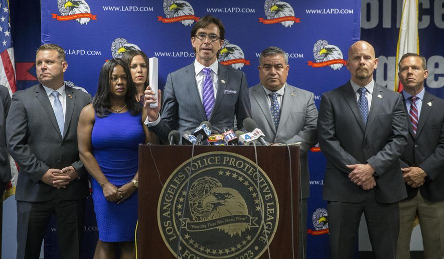 Attorney Gregg Adam, center at podium, surrounded by officials with Los Angeles Police Protective League, the union representing the rank and file of the Los Angeles Police Department, announce a lawsuit against the city and police chief during a news conference on Thursday, May 19, 2016, in Los Angeles.  The union filed a lawsuit in federal court, challenging the structure of the LAPD's Board of Rights, a three-person panel charged with deciding discipline cases for officers facing long-term suspension or termination. (AP Photo/Damian Dovarganes)