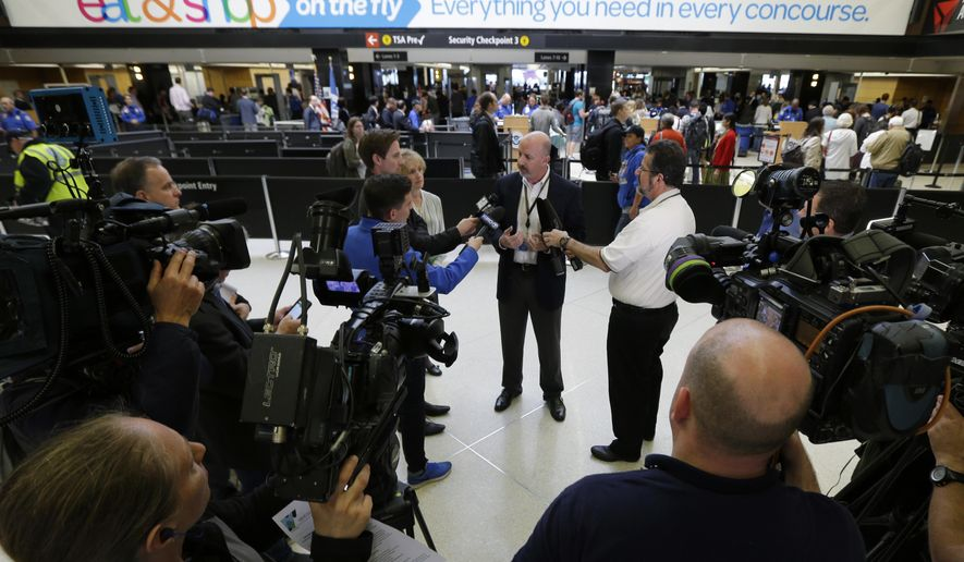 Daniel Zenk, center, senior operations manager for Seattle-Tacoma International Airport, talks to reporters in front of a security checkpoint, Thursday, May 19, 2016, in Seattle. Airport officials announced Thursday that following a training period, several dozen contract employees will start work on Monday, May 23, 2016 to assist passengers at security checkpoints, with the goal of freeing up TSA agents and reducing passenger wait times. (AP Photo/Ted S. Warren)