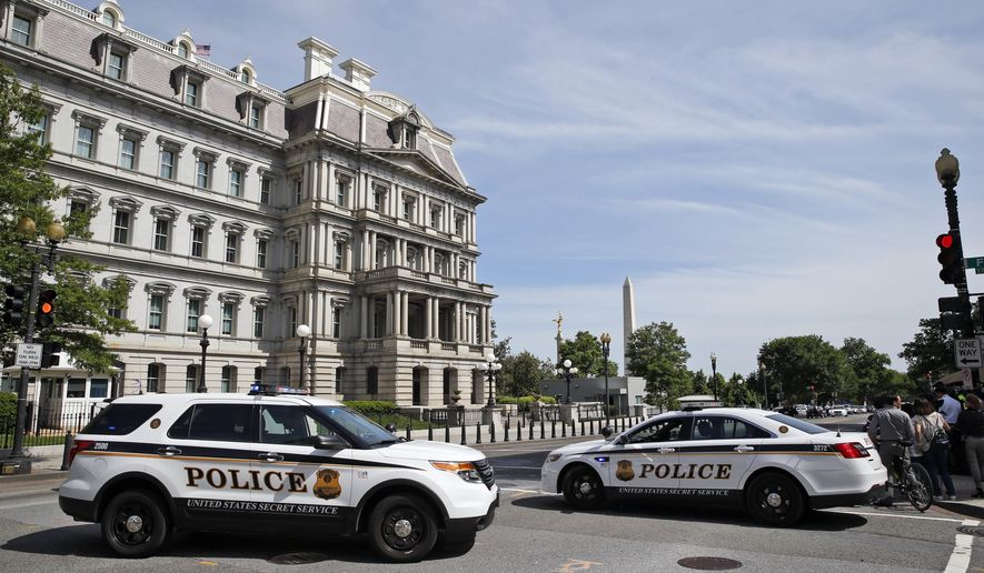 U.S. Secret Service officers block 17th Street next to the Eisenhower Executive Office Building in Washington, Friday, May 20, 2016, after the White House was placed on a security alert after a shooting on a street outside. (AP Photo/Alex Brandon)