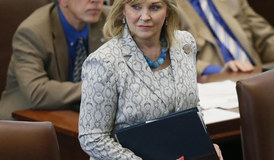 In this Wednesday, May 18, 2016 photo, Oklahoma Gov. Mary Fallin walks on the floor of the Oklahoma House in Oklahoma City. A bill awaiting Fallin's signature that would make it a felony for a doctor to perform an abortion has been described by critics as the first of its kind in the nation, but such measures are not uncommon in a state that GOP leaders like to describe as the reddest of the red.(AP Photo/Sue Ogrocki)