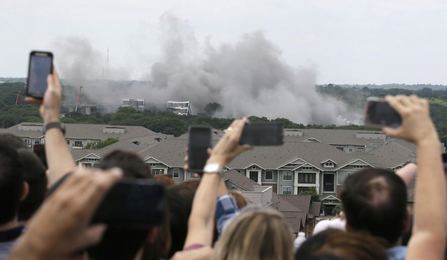 American Airlines employees look on and shoot video of the implosion of the company's former headquarters building in Fort Worth, Texas, Friday, May 20, 2016. (AP Photo/LM Otero)