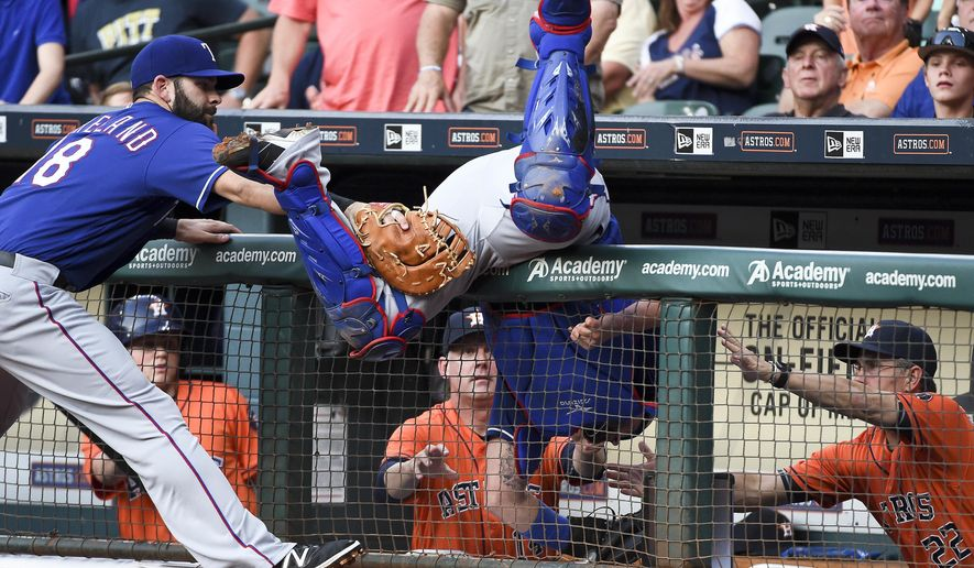Texas Rangers' catcher Bobby Wilson, center, falls into the Houston Astros' dugout attempting to catch the foul ball of Houston Astros' Jose Altuve as teammate Mitch Moreland, left, tries to prevent Wilson from falling over in the first inning of a baseball game, Friday, May 20, 2016, in Houston. (AP Photo/Eric Christian Smith)