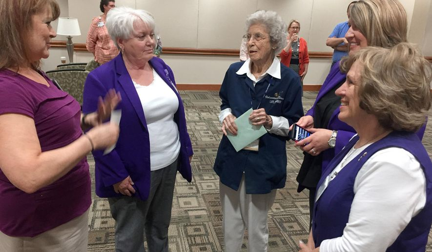 ADVANCE FOR WEEKEND EDITIONS MAY 21-22 - In this May 10, 2016 photo, Mary Hunter, third from left, talks with Forsyth Medical Center employees and volunteers at a celebration in her honor in Winston-Salem, N.C.. Hunter is retiring as a hospital volunteer after 44 years. She retired on her 100th birthday. With her are LaRee Hansel, left, Kitty William, second from left, Stephanie Owen, second from right,and Judy Blackburn.  (Richard Craver/The Winston-Salem Journal via AP) MANDATORY CREDIT