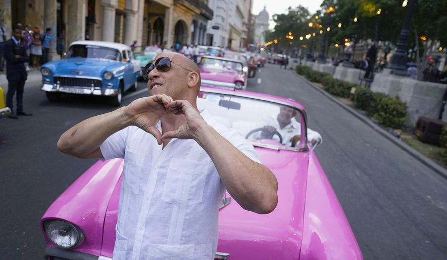 "FILE - In this May 3, 2016, file photo, U.S. Actor Vin Diesel flashes a heart-in-hand to the crowd ahead of the presentation of fashion designer Karl Lagerfeld's ""cruise"" line for fashion house Chanel, along Paseo del Prado street in Havana, Cuba. The mostly foreign audience arrived in specially hired classic American cars. Havana residents had to watch from behind police lines more than a block away.  (AP Photo/Ramon Espinosa, File)"