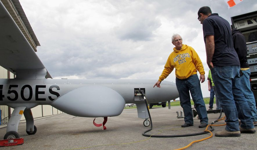 North Dakota State University agricultural researcher John Nowatzki points to a mechanical panel of a Hermes 450 drone before the aircraft took off from the Hillsboro, N.D. airport on Friday, May 20, 2016, to collect agriculture data. The drone can fly higher and longer than other aircraft currently being used for commercial purposes in the United States. The 20-foot long drone can fly for 20 hours. (AP Photo/Dave Kolpack)