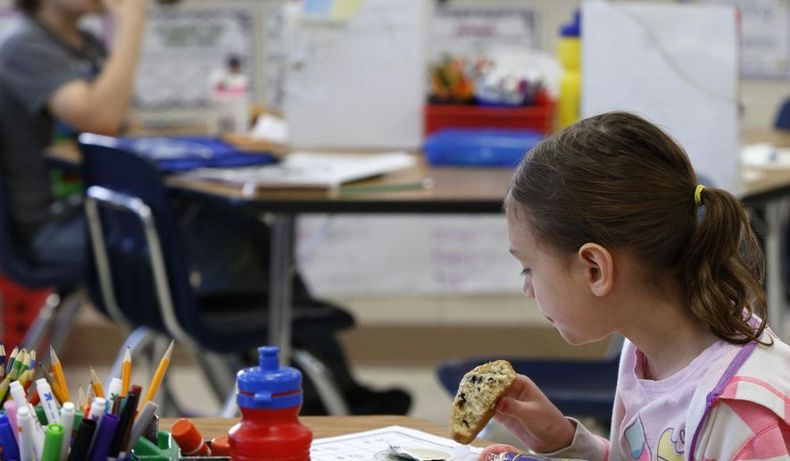 ADVANCE FOR WEEKEND EDITIONS MAY 21-22 - In this May 12, 2016 photo, Second-grader Ava Hart eats breakfast while working on a math worksheet in Libby Ettinger's classroom at Riverside Central Elementary School in Rochester, Minn. Riverside participates in the breakfast program which provides all students with free breakfast. School leadership says the program has reduced behavioral problems. (Andrew Link/The Rochester Post-Bulletin via AP) MANDATORY CREDIT