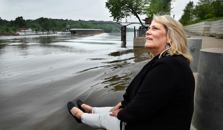 """FOR RELEASE MONDAY, MAY 23, 2016, AT 12:01 A.M. CDT. - Jody Martinez lifts her feet so as not to get wet from the wake of a passing barge on the Mississippi River at Chestnut Plaza in the Upper Landing Park in St. Paul, Minn. on Wednesday, May 11, 2016. """"This is a working river,"""" she said. """"People forget."""" Martinez, the lead designer of parks in a city known for them, is about to retire. (Jean Pieri/Pioneer Press via AP) MANDATORY CREDIT"""