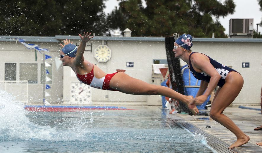 "In this image provided by USA Water Polo, Alys Williams, left, and Kaleigh Gilchrist , of the United States women's water polo national team take part in ""Flop Friday"" at the USA Water Polo National Training Center, Friday, May 20, 2016, in Los Alamitos, Calif. he U.S. women's water polo team is preparing for the Olympics this summer, and its weekly routine includes what the players have affectionately dubbed ""Flop Friday,"" when they line up and belly flop into the pool. (Sherie Key/USA Water Polo via AP)"