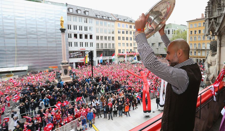 Josep Guardiola, head coach of Bayern Munich  celebrates  with the German  soccer Championship trophy  on the balcony of the  town hall at Marienplatz  square in Munich , Germany, Sunday May 15,  2016.  ( Alexander Hassenstein/ Pool Photo via AP)