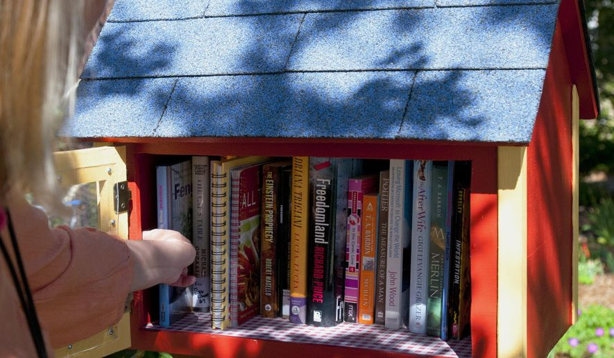 ADVANCE FOR WEEKEND EDITIONS - In this Thursday, May 12, 2016 photo, Jennifer Duncan sorts through books inside her little library outside her Logan, Utah, home. (John Zsiray/The Herald Journal via AP) MANDATORY CREDIT