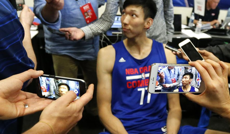 FILE - In this May 12, 2016, file photo, Zhou Qi, from China, is displayed on two mobile devices as he speaks with reporters at the NBA draft basketball combine in Chicago. Zhou needs a translator with him at workouts with NBA teams, simply because he does not speak enough English to understand most instructions. It doesn't seem to hold him back. Outside of Ben Simmons and Brandon Ingram, the 7-foot-2, sweet-shooting Zhou might command as much intrigue in this draft class as anyone else (AP Photo/Charles Rex Arbogast, File)