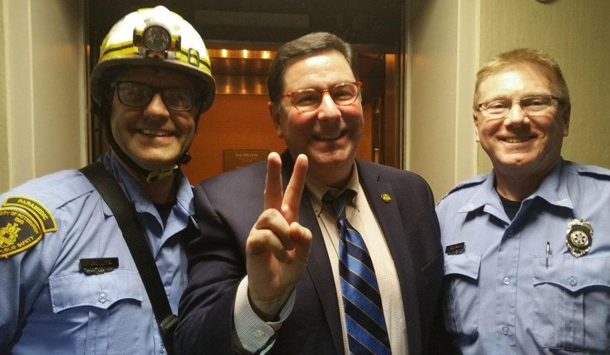 This photo provided by Pittsburgh Mayor Bill Peduto on Thursday, May 19, 2016 shows Peduto posing with two paramedics in Pittsburgh.  Peduto got stuck in the Westin Hotel elevator Thursday evening along with the mayors of Millvale and Leetsdale. They had been attending a meeting of the Allegheny League of Municipalities. It wasn't clear how they'd get out because none of the mayors, and a couple others stuck along with them, could get cellphone service.  One of the stranded passengers worked at the hotel and was able to summon maintenance crews and first responders using a walkie-talkie.(Pittsburgh Mayor Bill Peduto via AP)