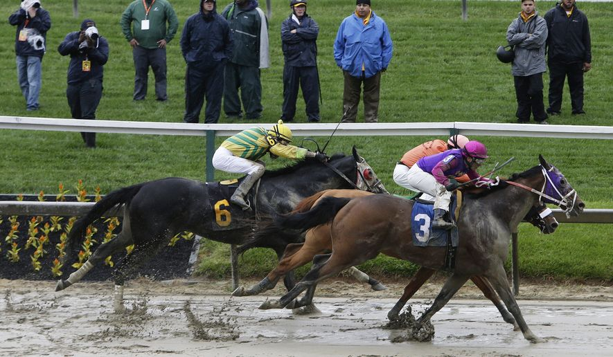 Homeboykris (3), ridden by Horacio Karamanos, moves to the finish in the first race of the day on a muddy track ahead of the 141st Preakness Stakes horse race at Pimlico Race Course, Saturday, May 21, 2016, in Baltimore. (AP Photo/Garry Jones)