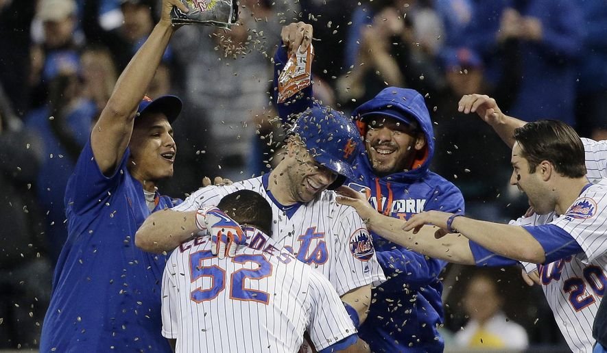New York Mets' David Wright, center, is showered with sunflower seeds by teammates after driving in the game-winning run with a bases loaded single in the ninth inning of a baseball game against the Milwaukee Brewers, Saturday, May 21, 2016, in New York. The Mets won 5-4. (AP Photo/Julie Jacobson)