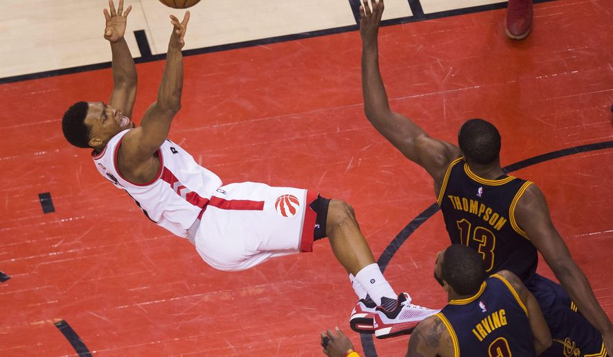Cleveland Cavaliers center Tristan Thompson (13) fouls Toronto Raptors guard Kyle Lowry, left, as Cavaliers guard Kyrie Irving (2) looks on during the second half of Game 3 of the NBA basketball Eastern Conference finals in Toronto on Saturday, May 21, 2016. (Nathan Denette/The Canadian Press via AP) MANDATORY CREDIT