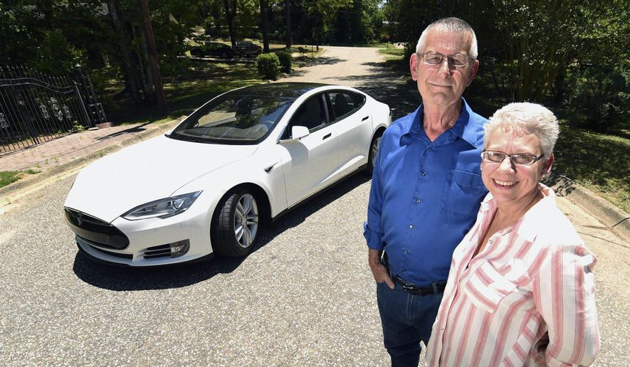 In this Saturday, May 14, 2016 photo, Tom and Elizabeth Wyse pose for a photo in front of their new Tesla at their home in Ozark, Ala. The Wyses said they can travel about 286 miles on a full charge. A typical charge on a residential charger is up to 52 miles of charge per hour, which could give a driver in need of a charge enough electricity to reach a free supercharging station provided in major cities along most interstates. (Danny Tindell/Dothan Eagle via AP) MANDATORY CREDIT