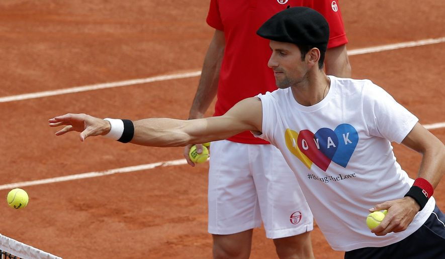 Serbia's Novak Djokovic wear a beret and a as he plays petanque before a training session of the French Open tennis tournament at the Roland Garros stadium, in Paris Saturday, May 21, 2016 . The French Open starts Sunday May 22. (AP Photo/Christophe Ena)