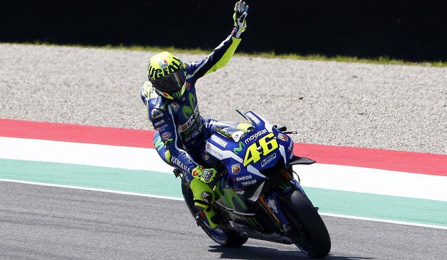 Yamaha rider Valentino Rossi, of Italy, celebrates after setting the pole position during the qualifying session for Sunday's Italy Moto GP race, at the Mugello circuit, in Scarperia, Italy, Saturday, May 21, 2016. (AP Photo/Antonio Calanni)