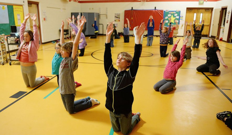 ADVANCE FOR SATURDAY, MAY 21, 2016 - In this Monday, May 2, 2016, photo, Nivin Maybon leads his classmates in morning yoga in Red Feather Lakes Elementary School in the northern Colorado mountain community of Red Feather Lakes. For the 150 students whose rural schools are tucked among the mountain forests west of Fort Collins, Colo., grade levels are combined into a handful of classrooms. (Valerie Mosley/The Coloradoan via AP) MANDATORY CREDIT