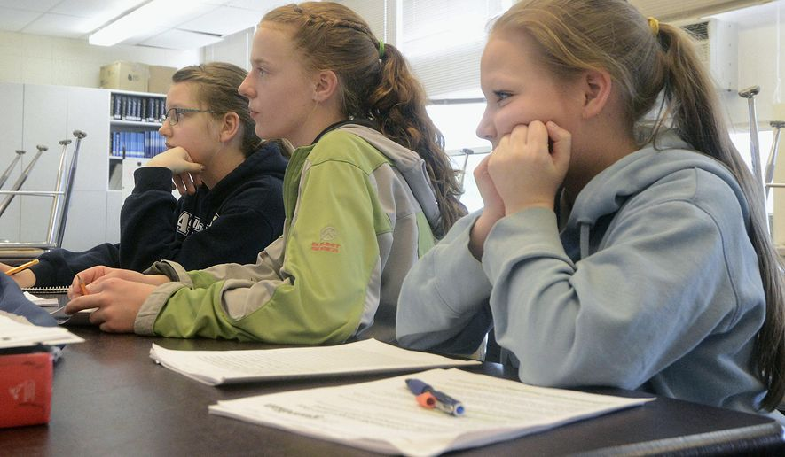 ADVANCE FOR WEEKEND USE MAY 21-22 AND THEREAFTER -  In this May 9, 2016 photo, Melita Efta, 12, from left, Bailey Epperheimer, 13, and Shelbie Naylor, 12, take in new information during a team practice session at Aurora Borealis Charter School in Kenai, Alaska. The girls and their fourth teammate will travel with an older group from Kenai Central High School to compete in the Future Problem Solving Program 2016 International Conference in Michigan in June. (Megan Pacer/Peninsula Clarion via AP) MANDATORY CREDIT