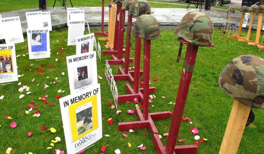 People pass a remembrance display that was part of a suicide-prevention walk Saturday, May 21, 2016, in Anchorage, Alaska. The display paid tribute to military members and others who have taken their own lives. (AP Photo/Rachel D'Oro)