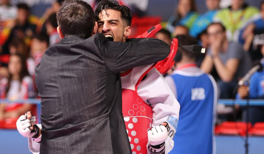 In this May 19, 2016 picture Belgium's Mourad Laachraoui , right, celebrates  after winning his fight against Spain's Jesus Tortosa Cabrera, during their men -54kg final at the European Taekwondo Championships in Montreux, Switzerland. (Daniel Mitchell/Keystone via AP)