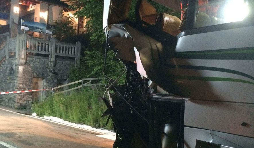 In this picture taken May 20, 2016 and provided by Bern police  a damaged Austrian bus stands on the road  after it crashed with a train at a railroad-crossing near Interlaken, Switzerland. Swiss police say at least 16 people were injured when a high-speed train crashed into a bus in Interlaken near Bern. Police said in a statement Saturday May 21, 2016  that the accident happened Friday night at a railway crossing.  (KANTONSPOLIZEI BERN via AP)   -MANDATORY CREDIT - NO SALES