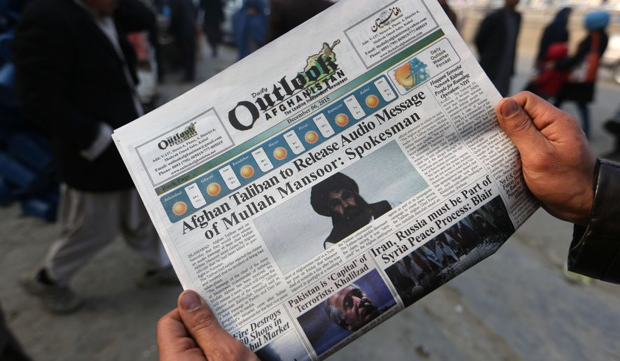 FILE - In this Dec. 6, 2015 file photo, an Afghan man reads a local newspaper with photos of the leader of the Afghan Taliban, Mullah Mansour, in Kabul, Afghanistan.  The Pentagon has announced that the U.S. has conducted an airstrike targeting Taliban leader Mullah Mansour. A U.S. official who wasn't authorized to publicly discuss the operation said Mansour and a second male combatant accompanying him in a vehicle were likely killed.  (AP Photo/Rahmat Gul)