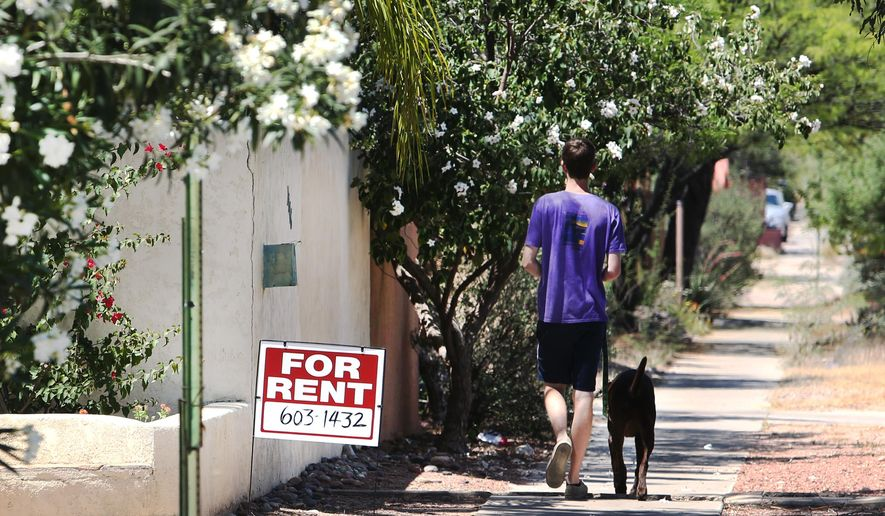 In this May 3, 2016 photo, a man walks his dog along a sidewalk in front of a property for rent in Tucson, Ariz. The University of Arizona and the city of Tucson are joining efforts to fill empty homes near campus with faculty and staff. (Mike Christy/Arizona Daily Star via AP) MANDATORY CREDIT