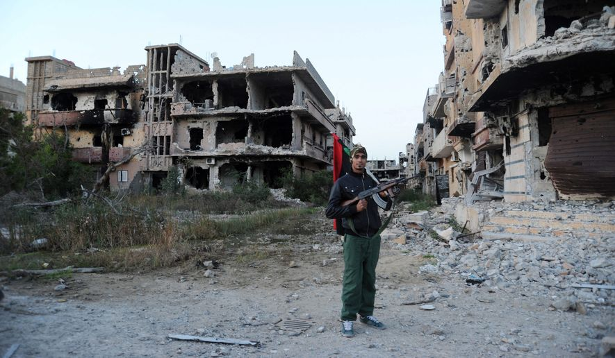 A civilian fighter roams an area of damaged buildings in Benghazi, Libya. The U.S. hopes its mission will bring unity to a fractured nation. (Associated Press)