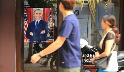 """A Vietnamese couple pass a poster of U.S President Barrack Obama with footnote read """"Welcome to our city"""", hanging in a door front in Hanoi, Vietnam on Sunday, May 22, 2016. Obama is expected to land in Hanoi on Monday for a three-day state visit to Vietnam. There's high hope for his visit, both from the government, which wants him to lift an arms export embargo, and from rights activists who want him to hold to account a leadership seen as treating its critics abysmally. (AP Photo/ Hau Dinh) (credit)"""