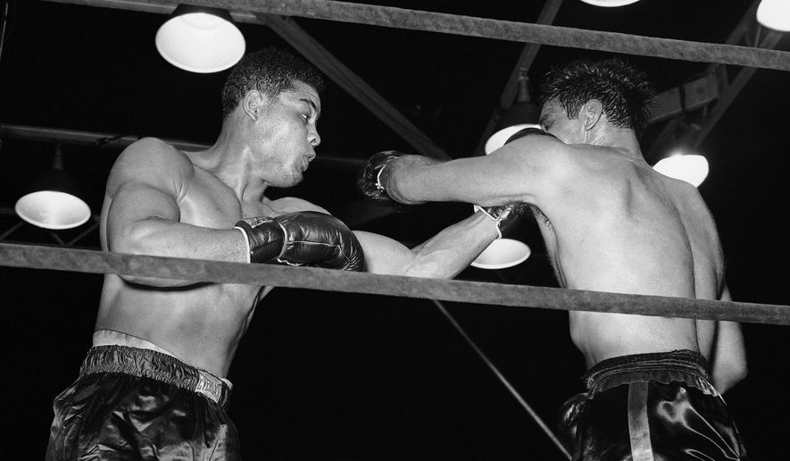 Although he held an advantage in reach, challenger Buddy Baer, right, ran into Joe Louis, left as he tried to land one of his own in their title go at Washington, May 23, 1941. Louis won when Baer was disqualified for refusing to answer the seventh-round well. (AP Photo/Charles Gorry)