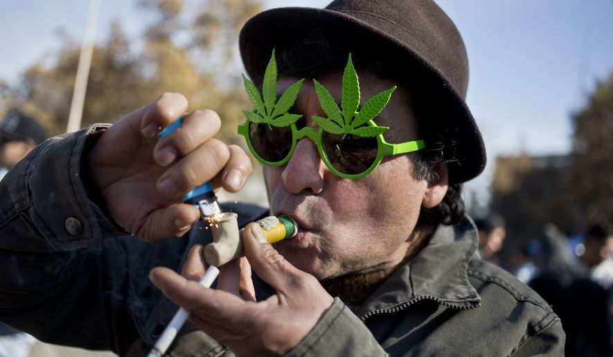 A man smoke marihuana during a demonstration in favor of the legalization of Marijuana in Santiago, Chile, Sunday, May 22, 2016. (AP Photo/Esteban Felix) ** FILE **